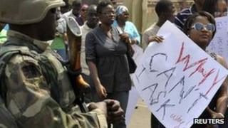 Fuel hike protesters pass a soldier in Abuja, Nigeria, 6 January