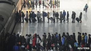 Passengers wait in lines to board their train at a railway station in Hefei, Anhui province, in China, 6 January 2012