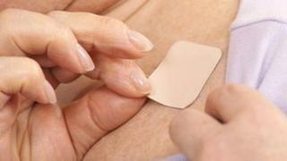 Woman putting on nicotine patch