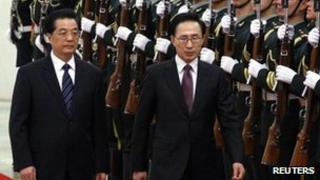 Lee Myung-bak (R) walks with Hu Jintao (L) as they inspect the guard of honour in the Great Hall of the People in Beijing, 9 January 2012