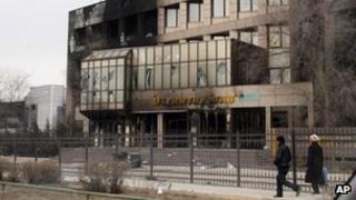 Residents walk past a burnt office in Zhanaozen, Kazakhstan (December 2010)