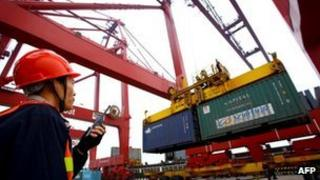 Worker operating hoists to unload containers at the Kaikou port, in south China's Hainan province, 8 January 2012