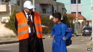 An Arab League monitor talks to a Syrian schoolboy in Deraa (Handout from Syrian state news agency - 3 January 2012)