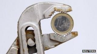Euro coin held in a pair of pliers