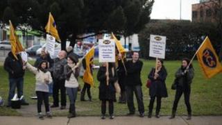 PCS (Public and Commercial Services) union members wave flags at cars near Heathrow Airport, west of London, on November 30, 2011, as they take part in a national strikes against pension cuts.