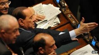 Silvio Berlusconi (gesturing) with other MPs in the Italian parliament, 12 January