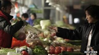 A customer pays for her vegetables at a market in Beijing, 12 January 2012