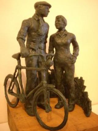 Miniature model of a statue showing man pushing a bike alongside a woman