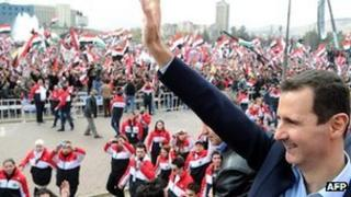 Syrian President Bashar al-Assad waves at supporters during a rare public appearance in Damascus on 11 January 2012