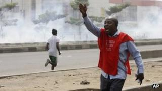 Protesters run away from tear gas fired by police officers during a demonstration against spiralling fuel prices in Lagos, Nigeria, Monday, Jan. 16, 2012.