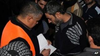 An Arab league observer writes the names of freed Syrian prisoners as they are released from Adra Prison on the north-east outskirts of Damascus