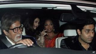 Indian actor Amitabh Bachchan drives with son Abhishek and daughter-in-law Aishwarya Rai (centre) in a car with Oprah Winfrey in Mumbai on 16 Jan 2012