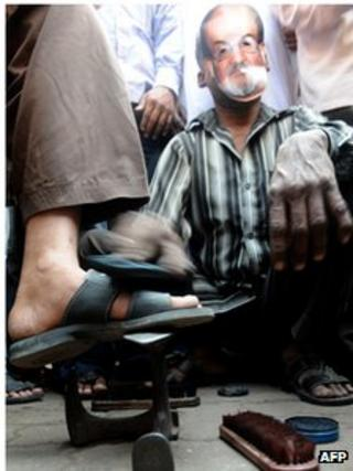 A cobbler wearing a mask of controversial British author Salman Rushdie polishes shoes outside a mosque during a protest by an Islamic organisation in Mumbai on January 11, 2011