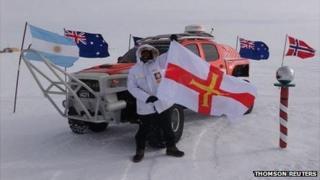 Jason De Carteret waving a Guernsey flag at the South Pole