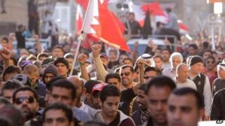 Mourners at a funeral for an anti-government protester wave Bahraini flags and chant anti-government slogans (15 January 2012)