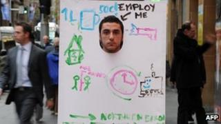 A student carrying an employ me banner