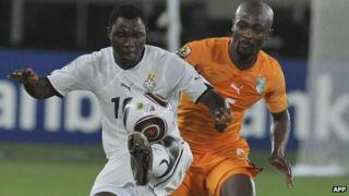 Ghana player Kwadwo Asamoah (L) duels for the ball with Ivory Coast's Didier Zokora