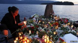 Woman lights candle to victims of Anders Behring Breivik on the shore opposite Utoeya island, Norway - 26 July 2012