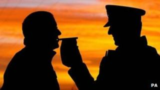 Silhouette of a motorist giving a breath test on a breathalyser for a police officer