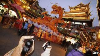 People look at decorations ahead the upcoming Chinese New Year of the Dragon in Shanghai, 19 January 2012