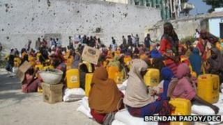 Dozens of Somali women sitting on sacks of food with oil containers