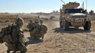 Soldiers crouching by a roadside in Afghanistan with an armoured vehicle