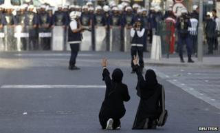 Bahraini women display victory signs to riot police in Manama (18 January 2012)