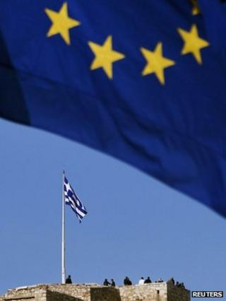An EU flag flies as tourists visit the ancient hill of Acropolis in Athens