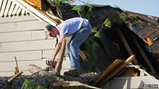 A man clears debris from a house after thunderstorms and possible tornadoes hit Alabama, 23 January 2012