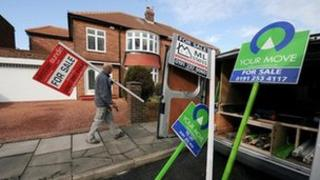 """Man erecting """"for sale"""" signs"""