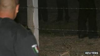 Police stand next to the body of a dead colleague in Ixtapaluca