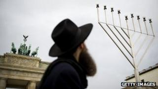 A Jewish man in front of a large menorah at the Brandenburg Gate in Berlin, Germany (file image)