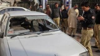 Policemen and security officials survey a damaged car used by lawyers as they were attacked by unidentified gunmen while they were travelling, at a Karachi police station January 25, 2012.