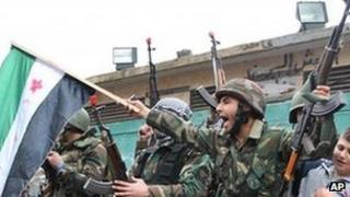 A Syrian army defector waves the Syrian revolution flag in Homs province, on Thursday, Jan. 26, 2012