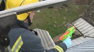 Firefighters use water pistols to spray the church roof