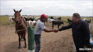 Venezuelan President Hugo Chavez shakes hands with a farm worker during his weekly radio and TV programme