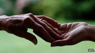 Young person touching hand of older person
