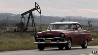 A man waves from his car as he drives by oscillating oil pumps operated by the state oil company Cuba Petroleos, January 2012