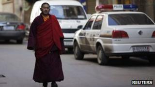 An ethnic Tibetan monk walks past a police station in Danba, Sichuan province on 26 January 2012