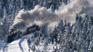 A narrow-gauge railway makes its way through a snow covered forest at the Harz national park near Schierke, central Germany