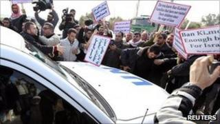 Palestinian protesters surround a vehicle in the convoy of UN Secretary General Ban Ki-moon as it arrives at Erez border crossing between Israel and Gaza on Thursday