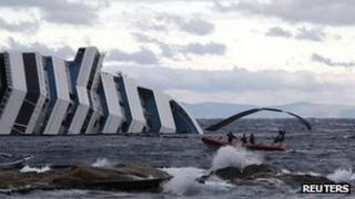 A coastguard approaches the Costa Concordia as a damaged oil boom flies in the wind on 1 February 2012