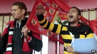 An injured fan (right) and his friend chant anti-military slogans in front of the al-Ahly club in Cairo. Photo: 2 February 2012