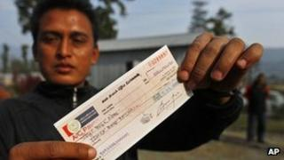 A former Maoist rebel displays a check presented by the government at Shaktikhor Maoist Camp in Chitwan, about 100 miles (160 km) south of the capital Kathmandu, Nepal, Friday, Feb. 3, 2012.