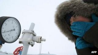 A women in Ukraine looks at a gas pressure monitor