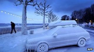 A man walks past an ice covered car on the frozen waterside promenade at Lake Geneva, Switzerland