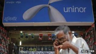 Man walks by a Uninor board in India