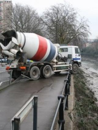 Lorry hanging over river wall