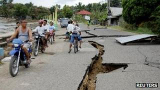 Residents drive past cracks in a road caused by an earthquake in Negros Oriental, central Philippines 6 February, 2012
