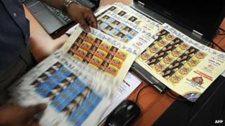 A postal employee sorts through ordered sets of special postage stamps featuring photographs of common citizens in Mumbai